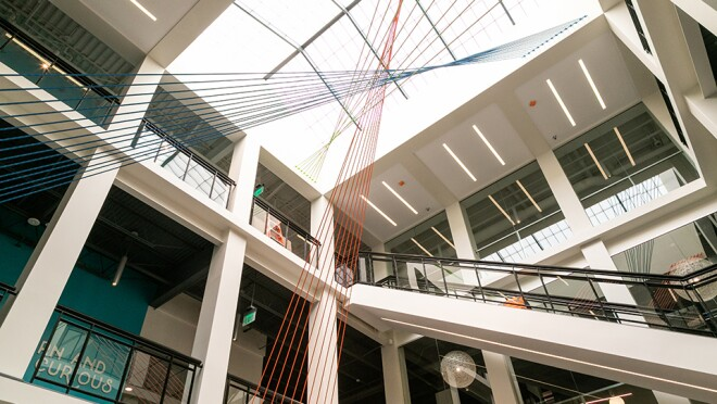 The inside of an office building, with glass ceiling to let light into the space, exposed ceiling spaces, glass-panel lined walkways. An art installation made of strings in orange, leaf green and blue take up the center space of the area.