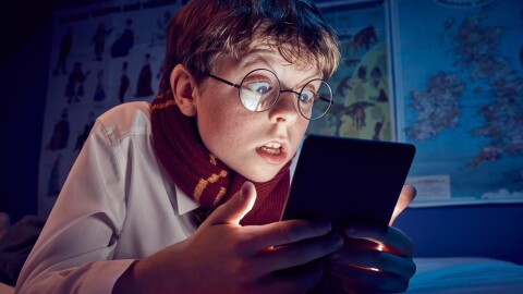 A boy with round glasses and a scarf reads a Kindle.