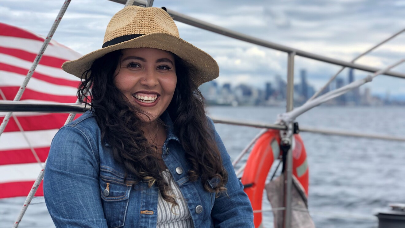 An image of a woman smiling for a photo while sitting on a sail boat. The American flag flies behind her on the boat.
