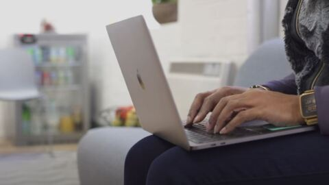 A woman types on the keyboard of a laptop computer while sitting on a sofa.