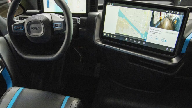 Digital displays and a steering wheel inside an Amazon electric delivery vehicle.