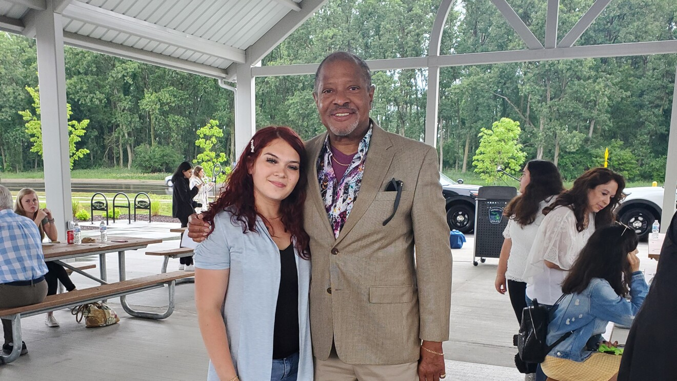 An image of a man and a woman standing together while smiling for a photo. They are at an event in a beautiful outdoor dining area.