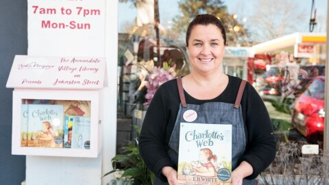 """An image of a woman holding the book """"Charlotte's Web,"""" while standing in front of a storefront that has a box on its door with books available for the community to borrow."""