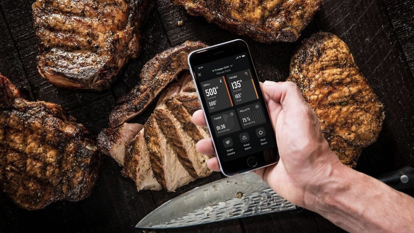 An image of a man holding a phone with the Traeger app open. Behind the phone in the photo is five large, grilled steaks and a large knife that has cut into one of the steaks.