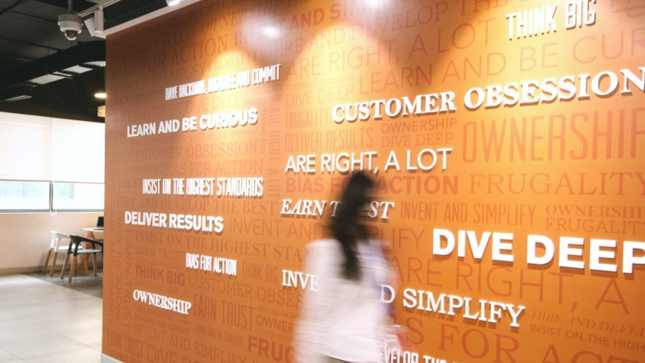 Amazon's Leadership Principles featured on a wall in an Amazon office building. A woman is walking in front of them.