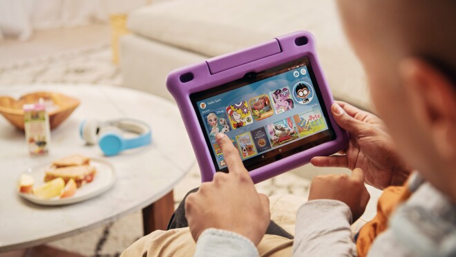 A father and child play with a Fire HD8 kids edition tablet together, in the foreground a snack awaits.