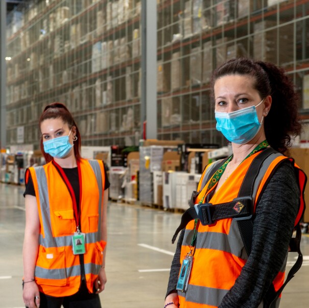 Two women, standing inside an Amazon fulfillment center, wear orange safety vests and masks while looking at the camera.
