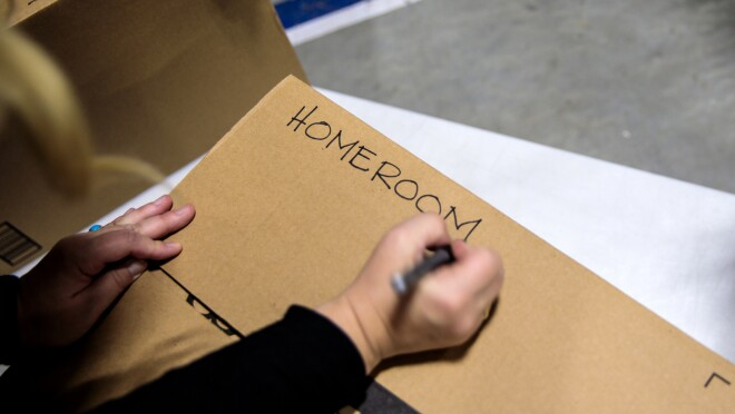 """A person holding a marker in their right hand writes """"homeroom"""" in capitalized block letters on a cardboard box."""