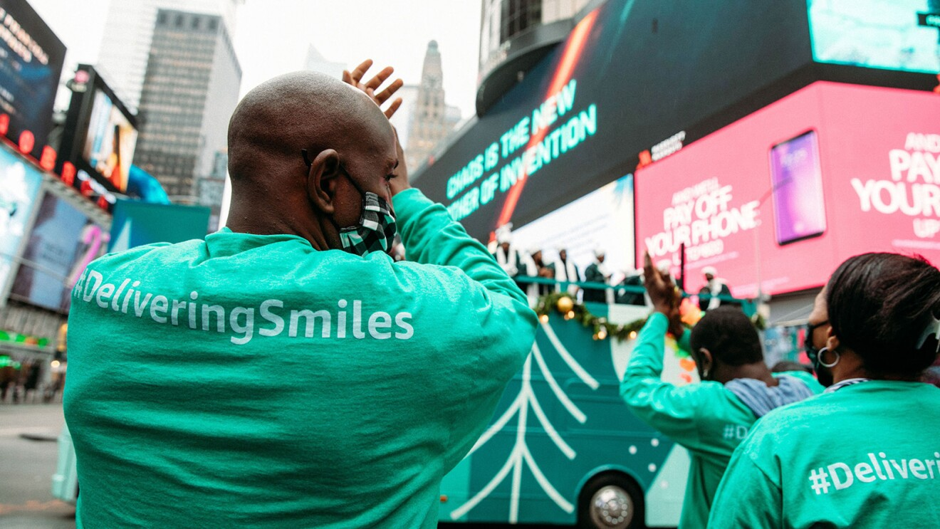 An image of a man clapping and smiling while wearing a mask and watching a choir perform on top of a double-decker bus.