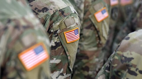 U.S. solidiers stand in close quarters, their shoulders baring a U.S. flag patch, their faces are obscured.