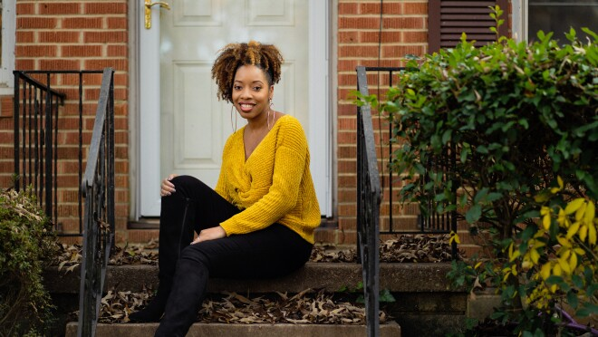 A woman, Crystal Swain-Bates, sits on the front step of a brick home. She waers black booties, black pants, a mustard yellow sweater, and large good hoops.