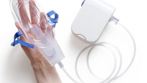A hand holding an oxygen mask