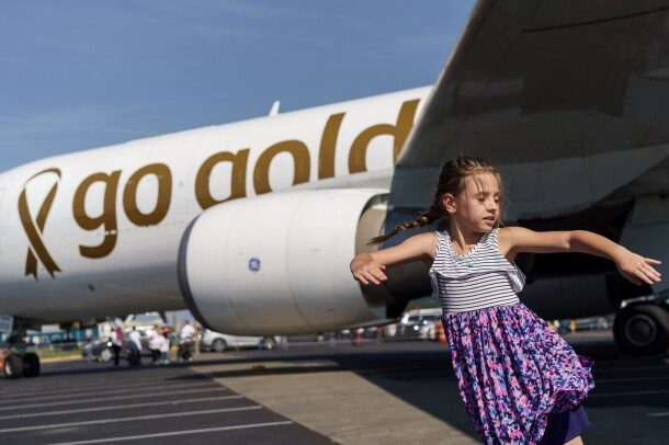 A young girl wearing a striped and floral dress, dances on the tarmac, in front of a Prime Air aircraft with go gold messaging on it.