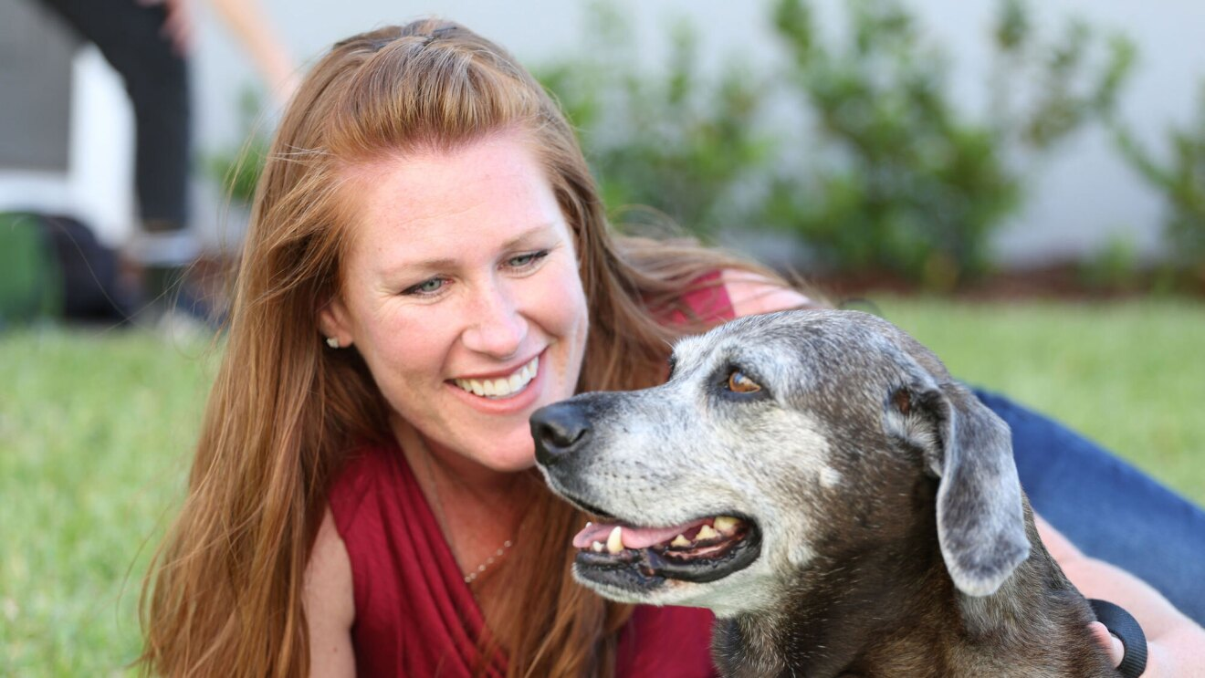 A woman with red hair smiles and hugs her dog.