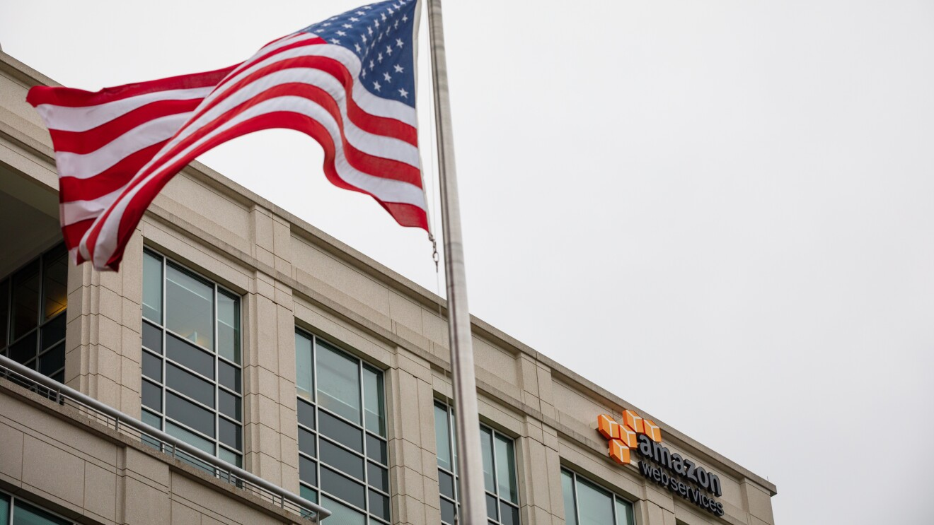 The United States flag moves in the wind in front of an Amazon Web Services building.
