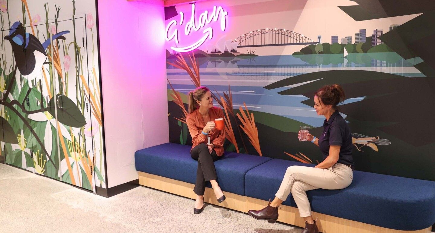 Two women who are Amazon employees engage in a conversation in a shared workspace in our Sydney, Australia office.