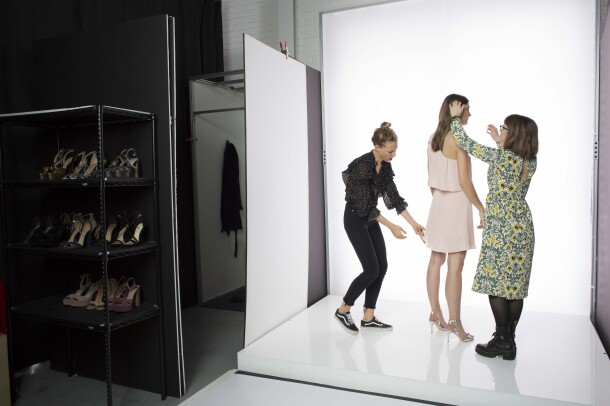 Amazon Fashion assistants assist a model wearing a pink dress and silver high heels during a photo shoot. The background is white.
