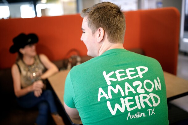 "An Amazonian sits, facing away from the camera, in the Austin, TX Amazon office. The back of his shirt says ""Keep Amazon weird - Austin, TX."" Across the table sits another person, wearing a tank top, jeans, and brimmed hat."