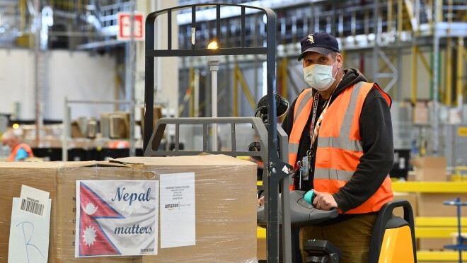Amazon employees work together inside a fulfillment center in Germany to gather supplies for disaster relief aid to Nepal.