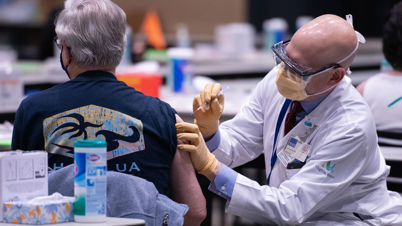 A man wearing a t-shirt receives a COVID-19 vaccination from a man wearing a Virginia Mason lab coat, mask, and gloves.