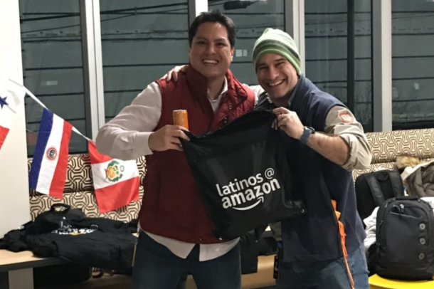 Two Amazon employees smile while holding up a backpack with the Latinos@ Amazon logo on it.