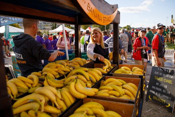 """The Community Banana Stand is shown in the foreground of this photo, with stacks of bananas available for attendees, for free, attended by two """"bananistas."""" In the background, event attendees are seen walking and standing."""