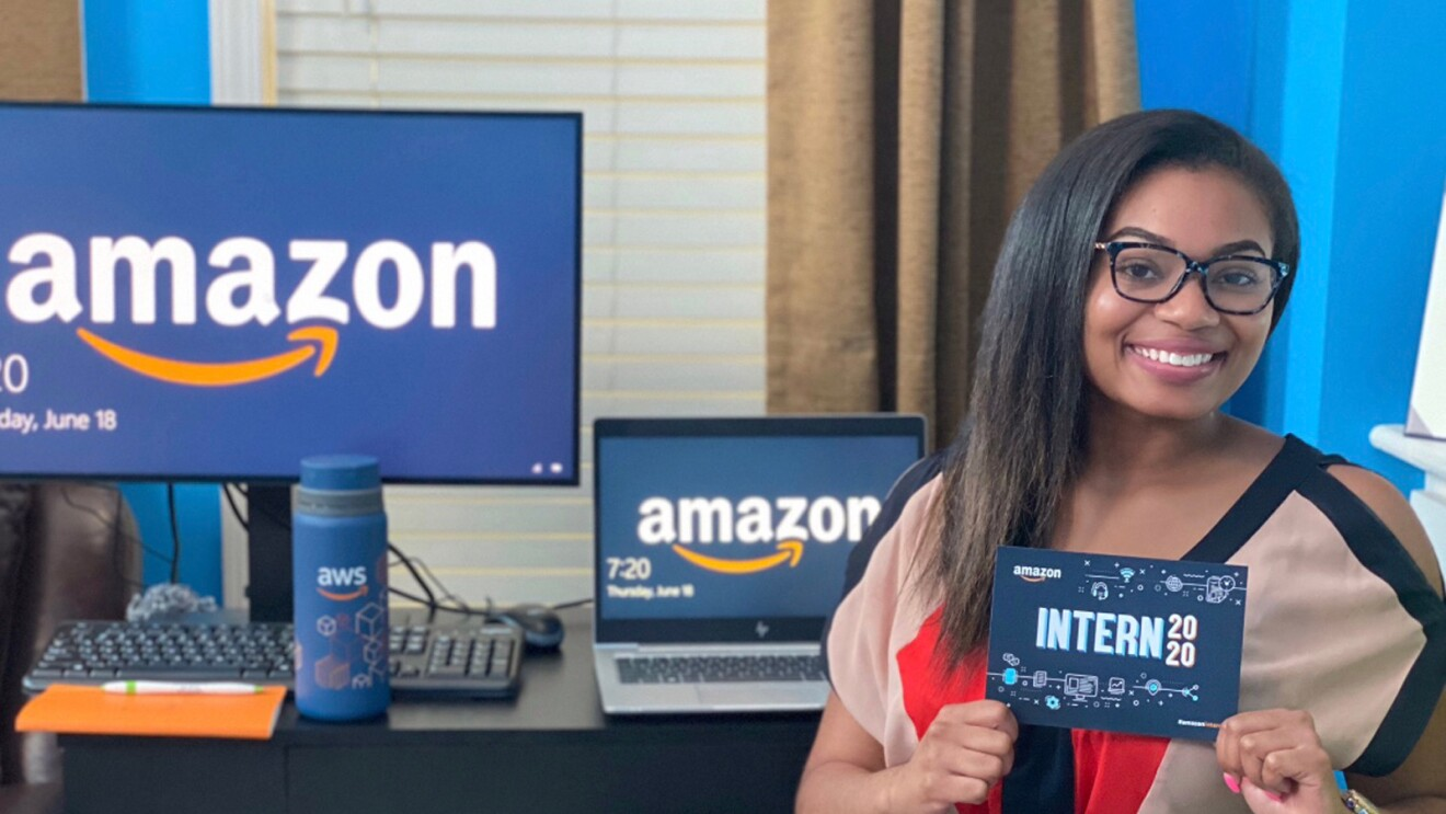 """A woman sits in front of a desk. She holds a card that says """"Amazon intern 2020."""""""