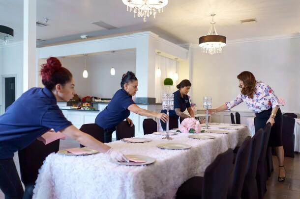 Four women set plates, napkins, and centerpieces on a long banquet table.