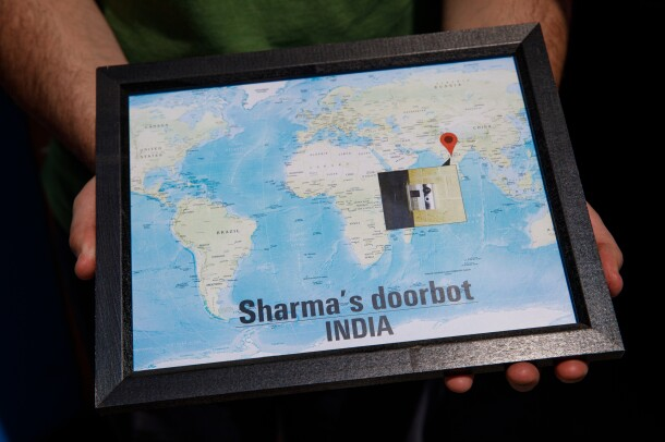 A framed map with a photo of a door showing an early Ring customer, Sharma in India.