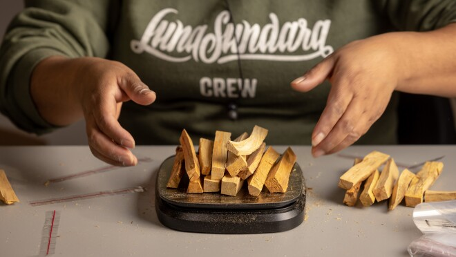 Close photo of hands of person weighing pieces of wood on a small scale.
