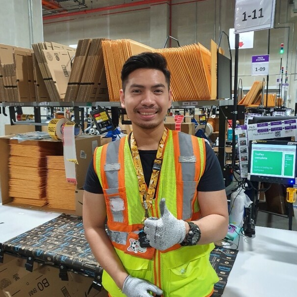 Aung Kaing giving a thumbs up in the fulfillment centre in Singapore