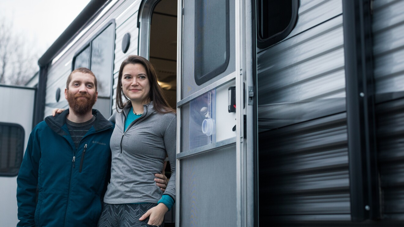 A man and woman stand just outside the door of a silver and gray RV.