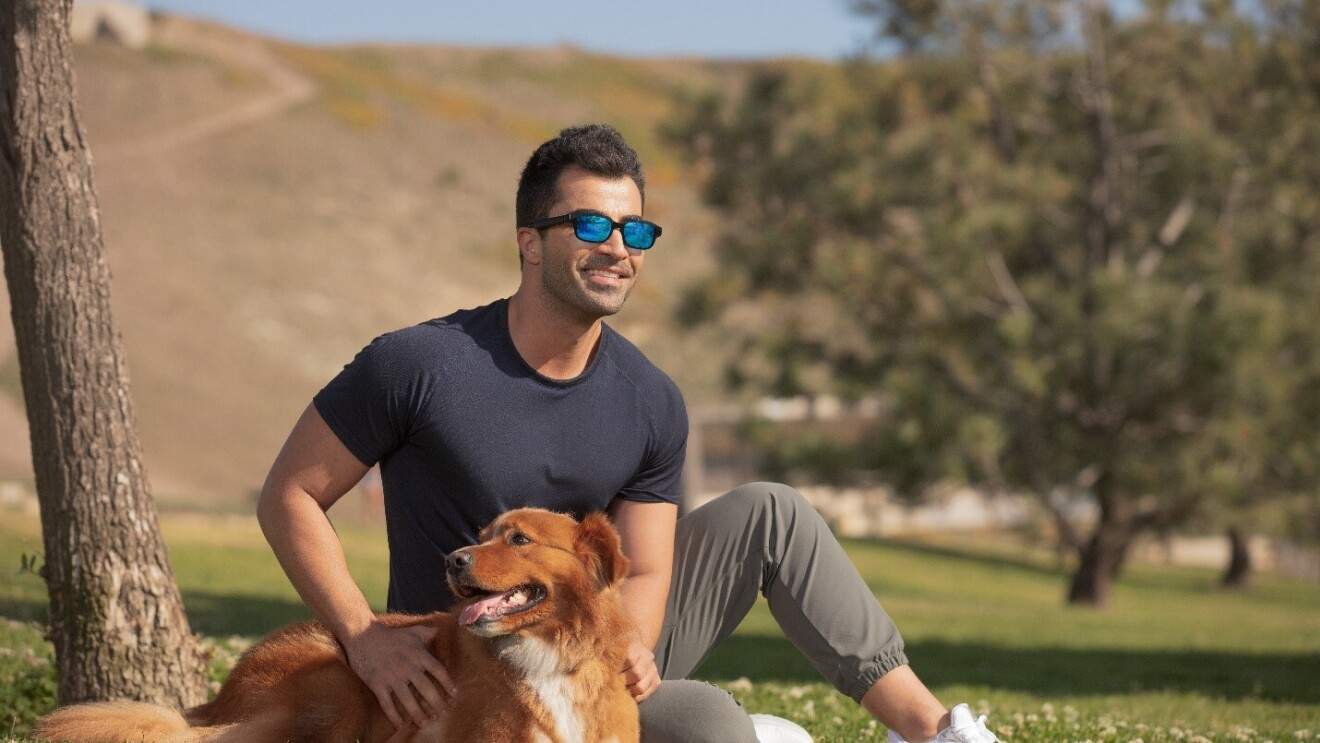 A man wears Echo Frame sunglasses while he sits outside with his dog.