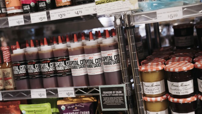 Capital City Mambo Sauce sits on the shelf of a retailer alongside other grocery products.
