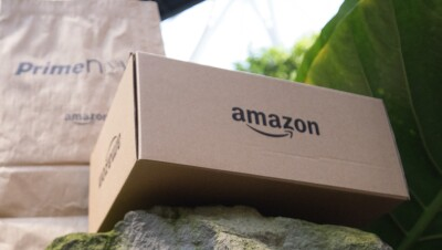 An Amazon package is positioned on a rock in the Spheres building with a Prime Day package behind it.