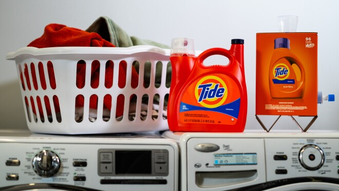 A basket of laundry sits atop a washer and dryer. Next to the laundry basket there are two containers of Tide laundry detergent. One is made of plastic. The other is made of cardboard and sits atop two triangular legs.