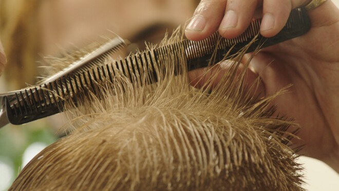A close up image of the top of a head of someone getting their hair cut.