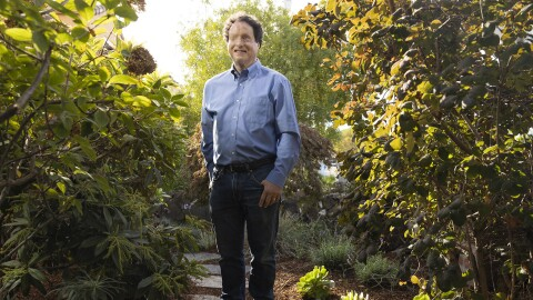 Josh Miele, Principle Accessibility Researcher at Amazon Lab126, stands for a portrait in a garden outside his home.