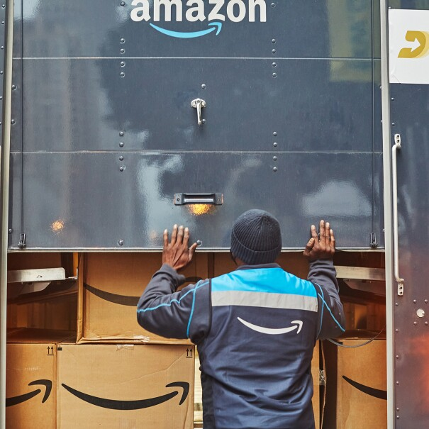 An image of a man closing the back of an Amazon delivery truck that is loaded with Amazon boxes inside of it.