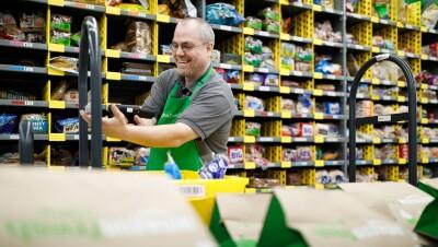 An Amazon associate fills grocery bags in an Amazon Fresh fulfillment center
