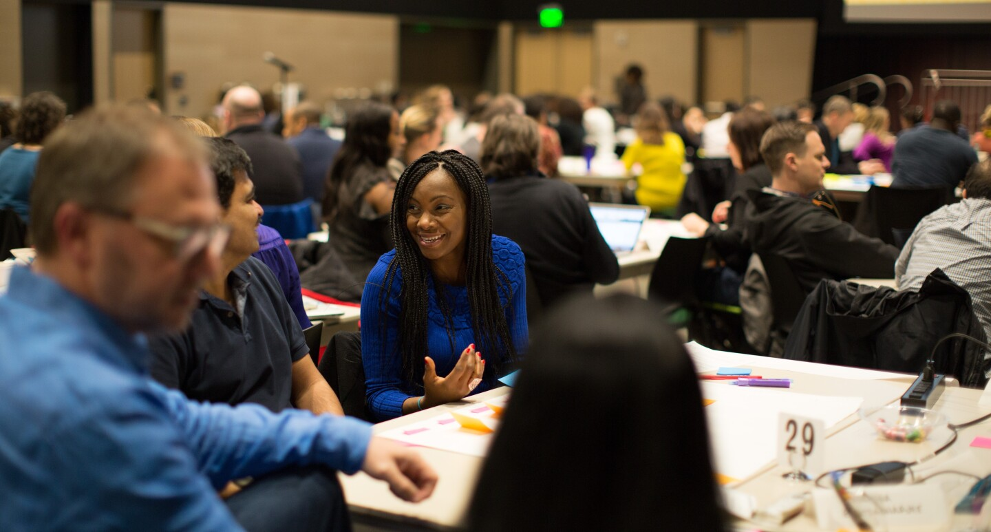 Men and women gather together at tables in a conference setting