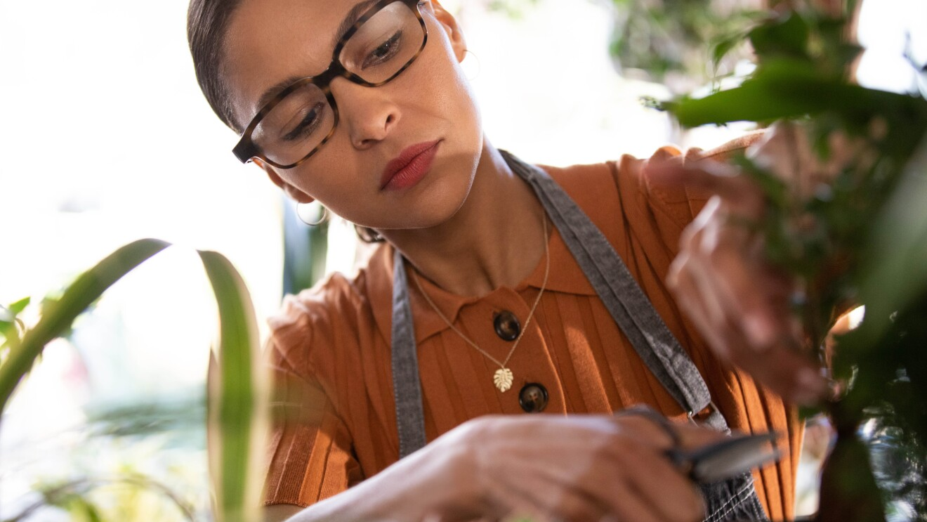 An image of a woman tending to plants while wearing her Echo Frames glasses.