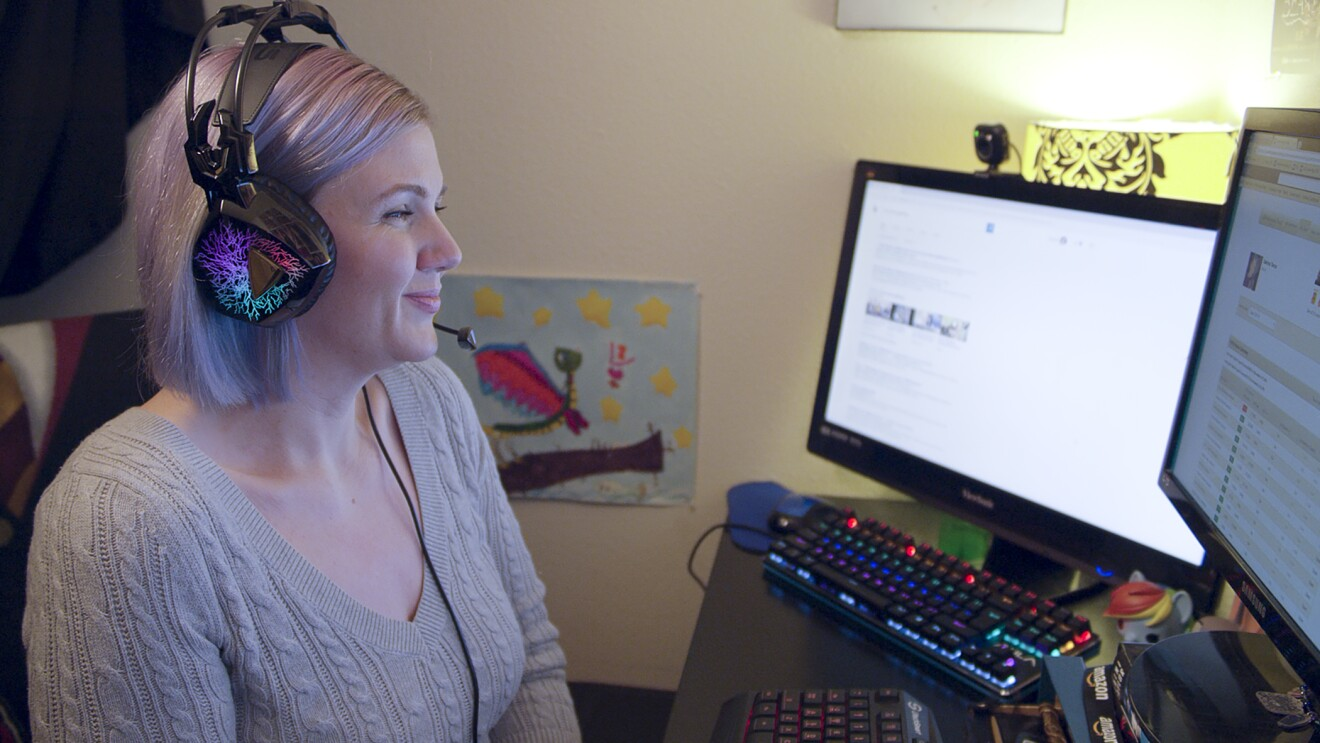 A woman wears a headset while looking at two computer monitors.
