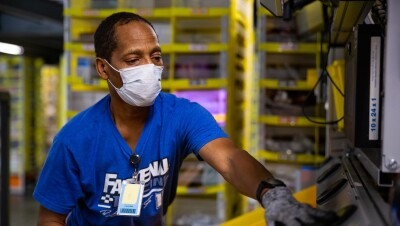 A man works while wearing gloves and a mask that covers his mouth and nose.