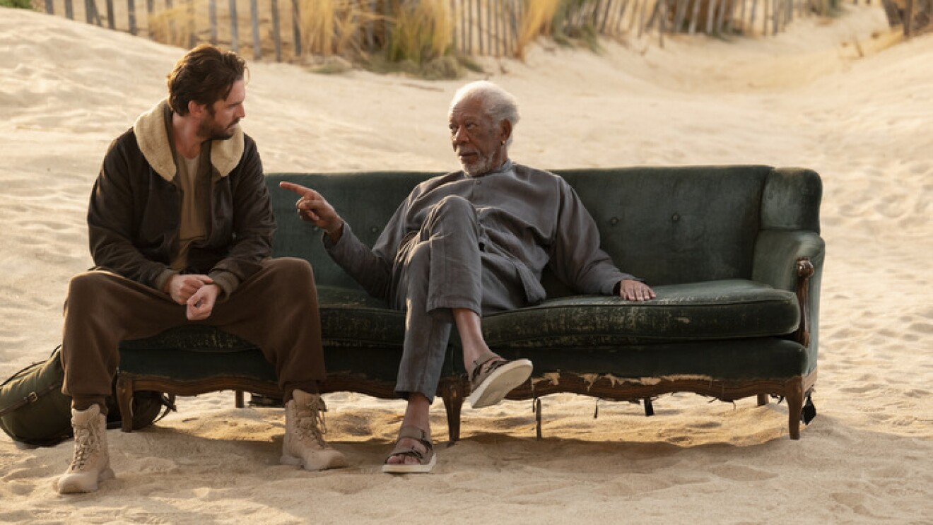 An image of Morgan Freeman and Dan Stevens sitting on a couch on a beach talking to each other. Freeman is pointing at Stevens casually as he speaks.