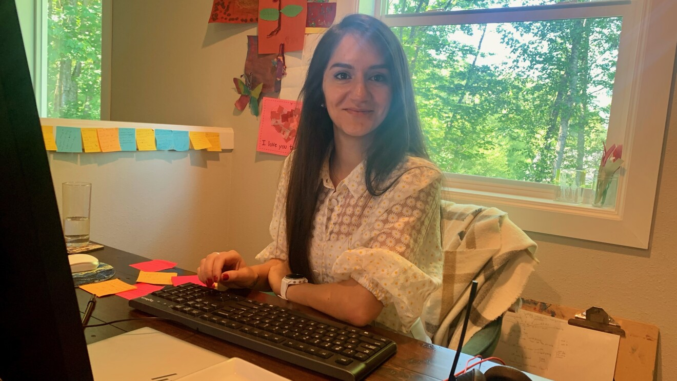 A woman smiles for a photo while sitting at her desk at home working.