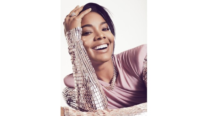Gabrielle Union smiles wearing a silver bejeweled shirt.