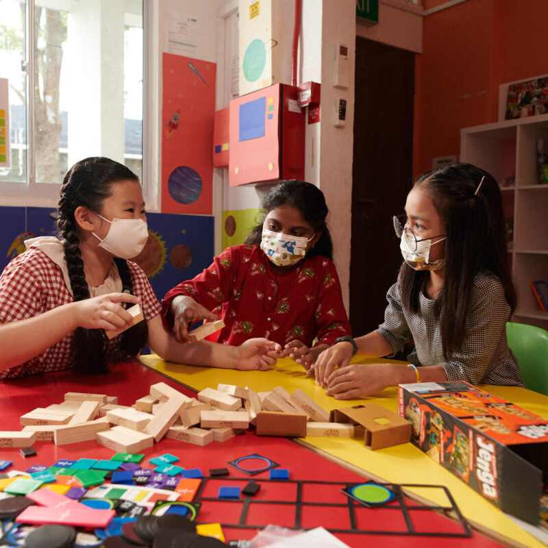 Three young children playing with toys that have been donated to NPOs as part of Amazon.sg's Delivering Smiles campaign
