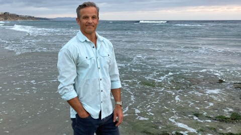 Author Dan Sheehan stands on an ocean beach wearing jeans and a button-down shirt.
