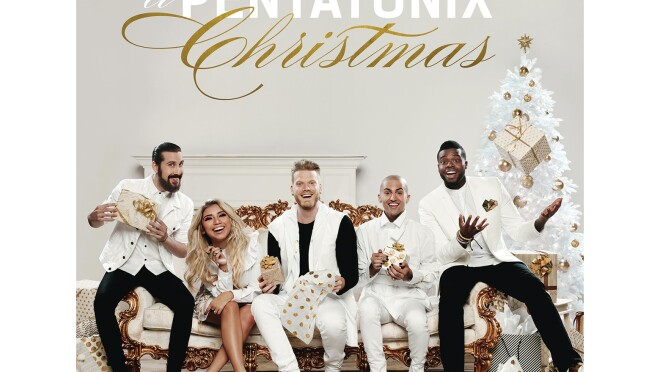 The members of Pentatonix sit on an oppulent ivory sofa with gold trim. A male in white button down with jacket and black pants sits next to a blonde woman leaning forward. She wears a white dress and flats. A man holds a gift, and wears white pants, black tee and white vest. A man in white tuxedo sits next to him and holds a gift. A man throws a gift up in the air. He wars a white tuxedo jacket with black and gold pocket square, white button down and tie and black pants.